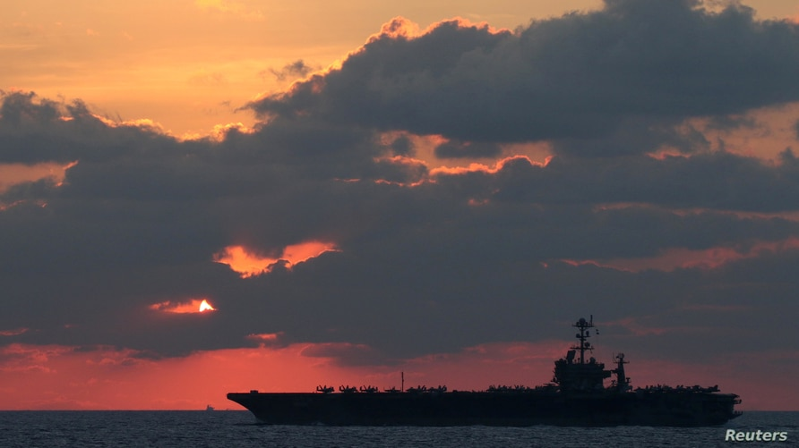 The U.S. Navy aircraft carrier USS John C. Stennis transits the South China Sea at sunset, February 25, 2019. Picture taken…