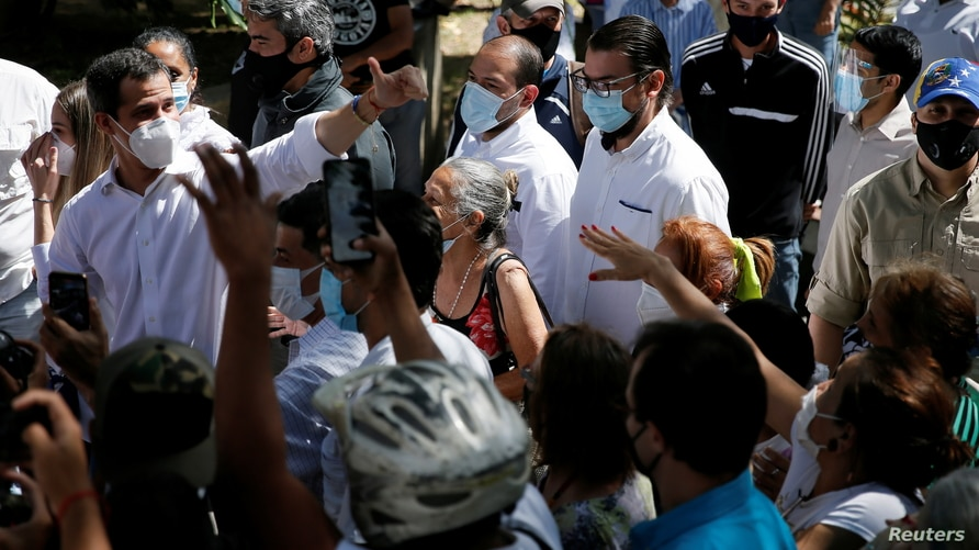 Opposition leader Juan Guaido greets supporters during a visit to a voting center during a popular consultation meant to reject…