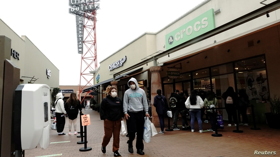 A couple walks past shoppers queuing to a Crocs store at  Citadel Outlets as the coronavirus disease (COVID-19) cases surge in…