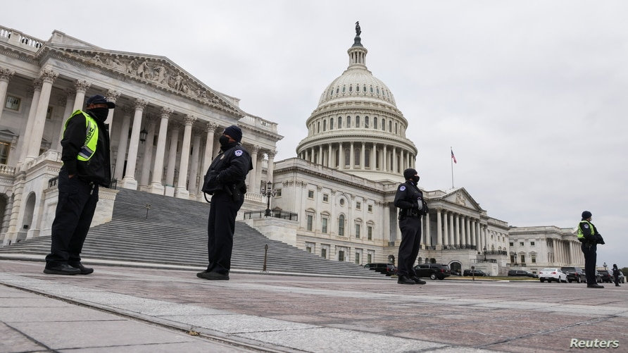 U.S. Capitol Police stand guard on a plaza surrounding the Capitol before Congress meets to certify the electoral college vote…