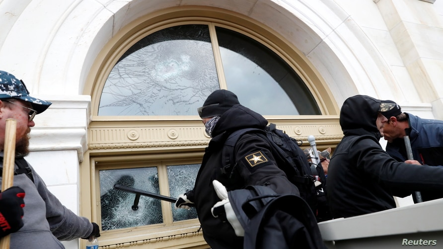 A pro-Trump protester smashes a window of the U.S. Capitol Building during clashes with Capitol police at a rally to contest…