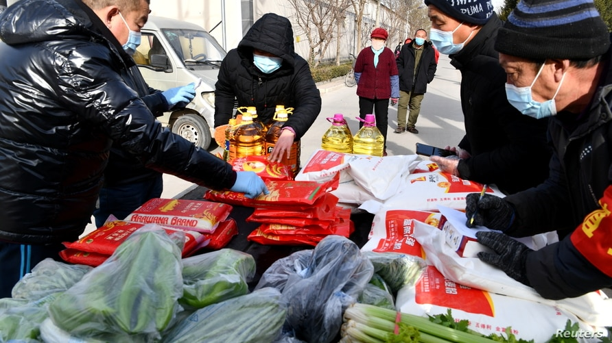 Volunteers distribute groceries to villagers at an entrance to Longhua village, following a recent outbreak of the coronavirus…