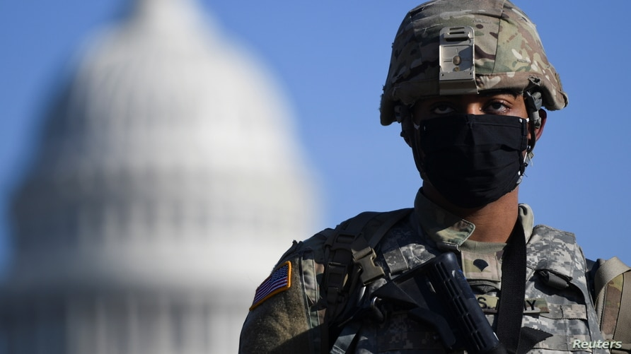 A member of the National Guard mounts guard near the U.S. Capitol building, as the House of Representatives debates impeaching…