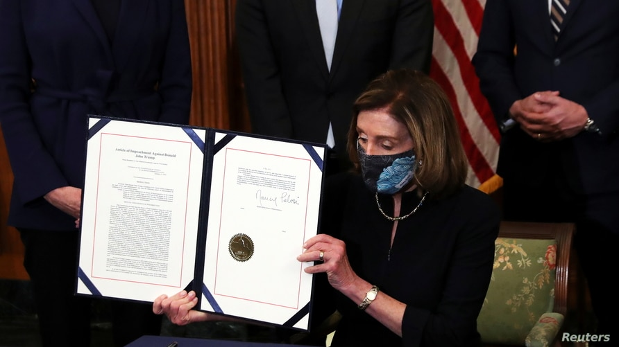 U.S. House Speaker Nancy Pelosi (D-CA) shows the article of impeachment against U.S. President Donald Trump after signing it in…