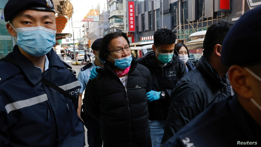 Daniel Wong Kwok-tung, a lawyer who tried to help the 12 people detained in mainland China, is escorted by police as he returns…