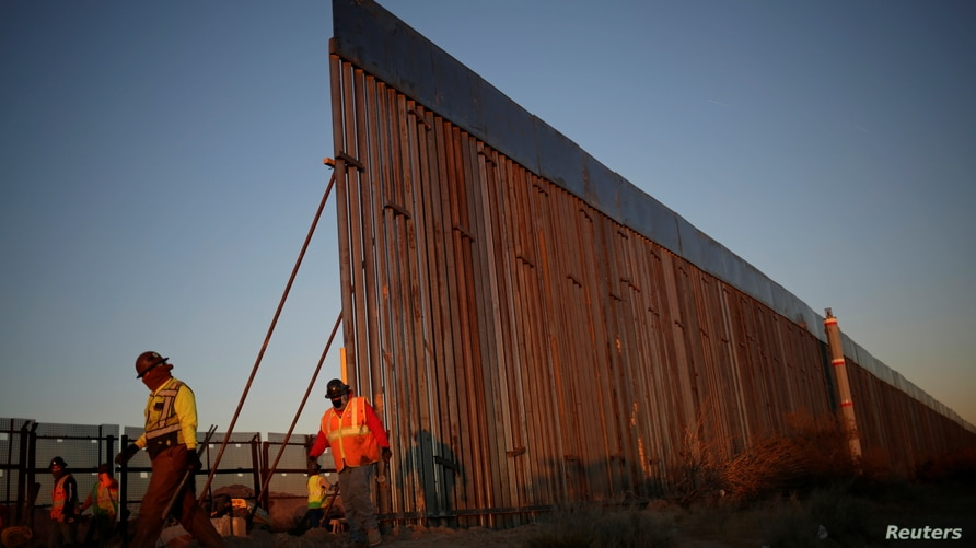 Members of a construction crew work on a new section of the bollard-type border wall in Sunland Park, New Mexico, U.S., as seen…