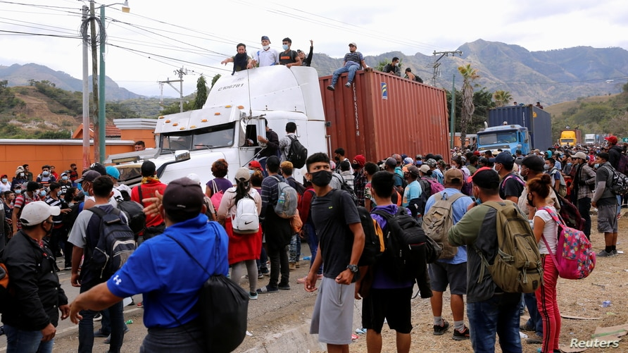 Honduran migrants, some of them riding on top of trailer trucks, try to cross a police checkpoint to continue their trip along…