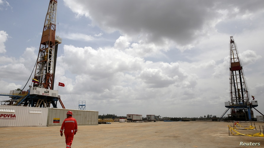 FILE PHOTO: An oilfield worker walks next to drilling rigs at an oil well operated by Venezuela's state oil company PDVSA, in…