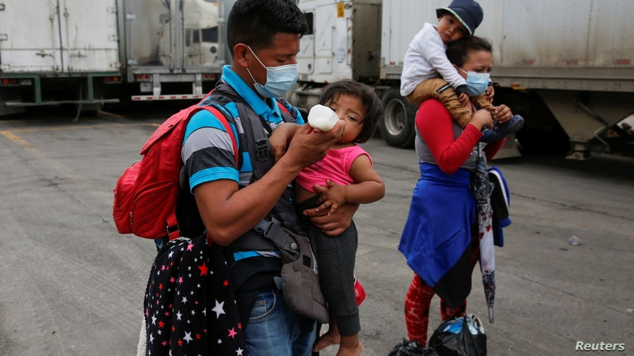 A Honduran migrant who was trying to reach the U.S. feeds a child as the migrants are sent back by Guatemalan authorities, at…