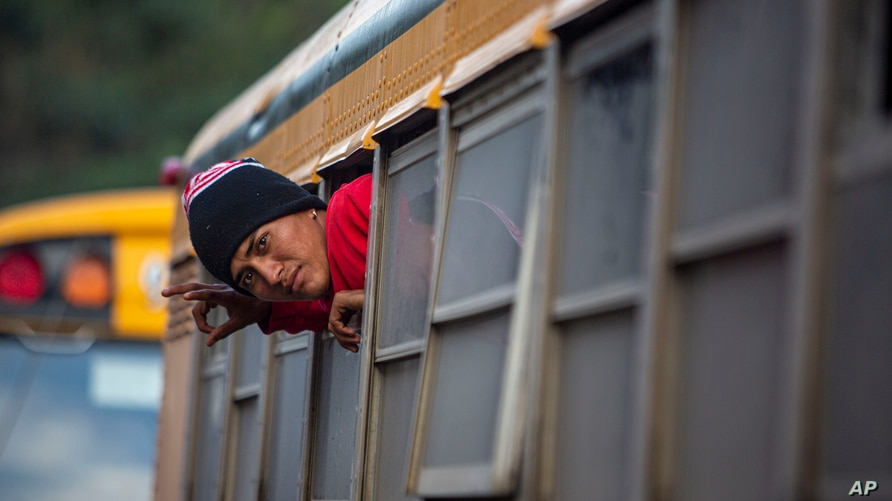 A Honduran migrant peers from a bus that will take him and other migrants to San Pedro Sula, from Copan, Honduras, after…