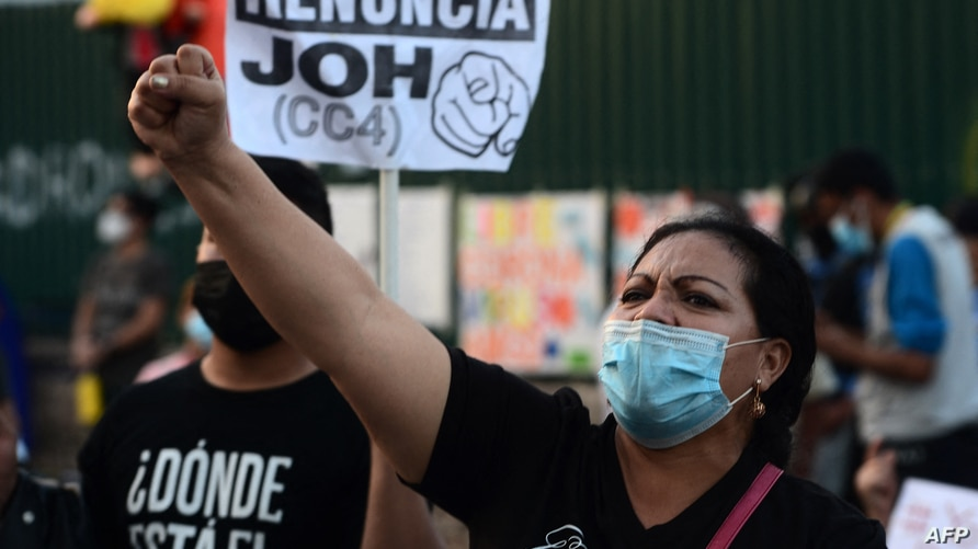 A woman raises her fist as she takes part in a protest in demand of the resignation of Honduran President Juan Orlando…