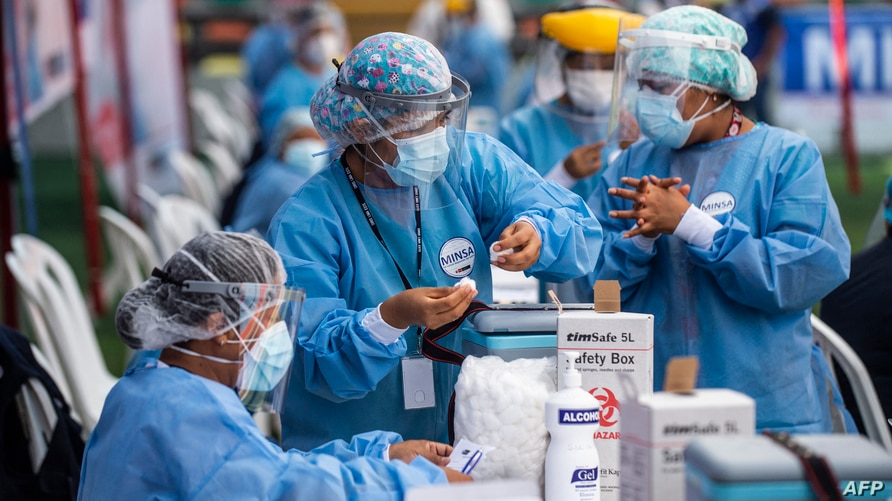 A nurse prepares a dose of the vaccine developed by Sinopharm of China against COVID-19 during a health workers vaccination…