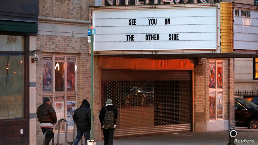 People walk by the Nitehawk cinema, which is closed due to the coronavirus disease (COVID-19), shortly before Governor Andrew…