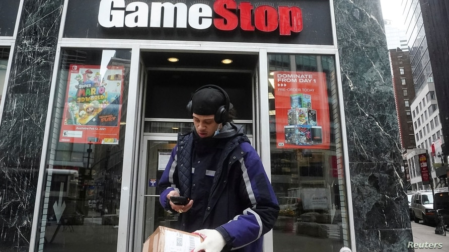 FILE PHOTO: A Fedex deliveryman prepares a package for a GameStop store amid the coronavirus disease (COVID-19) pandemic in the…