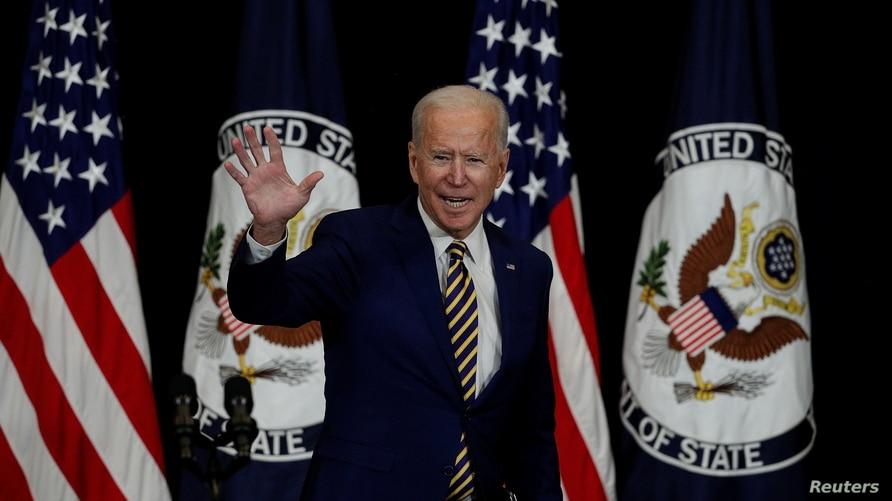 U.S. President Joe Biden waves after speaking to State Department staff during a visit by Biden at the State Department in…