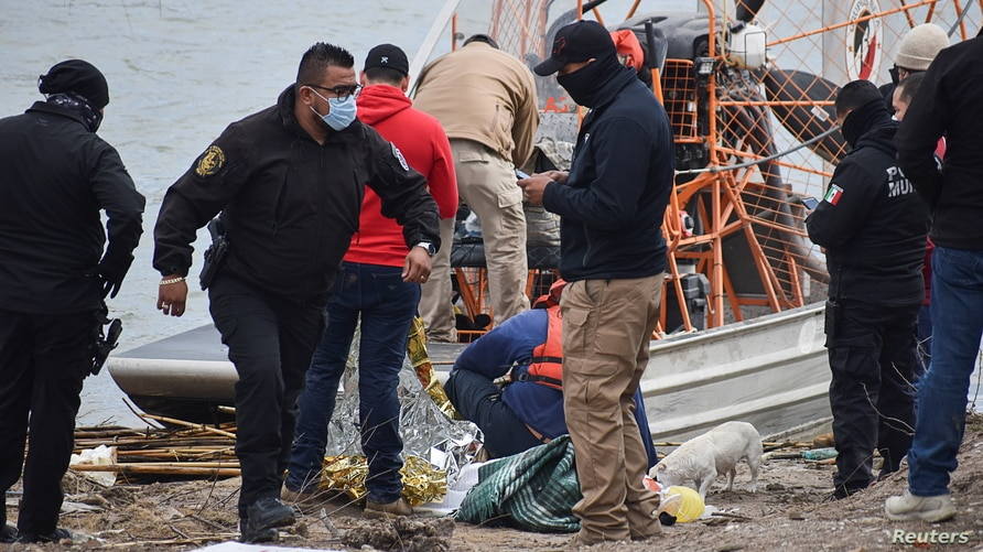Paramedics check the body of a Honduran migrant child, who drowned while crossing the frigid waters of the Rio Grande river…
