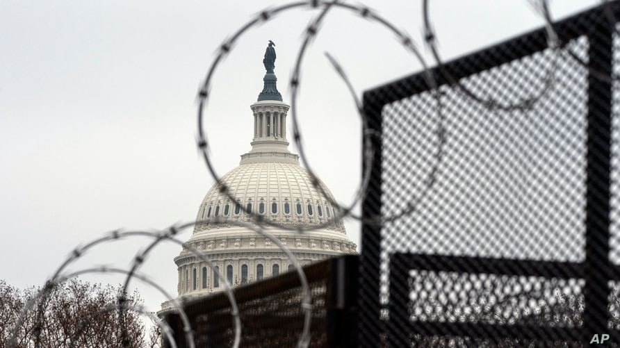 Razor wire tops the anti-scaling fence surrounding the permitter of the U.S. Capitol, Thursday, Feb. 11, 2021, in Washington. …