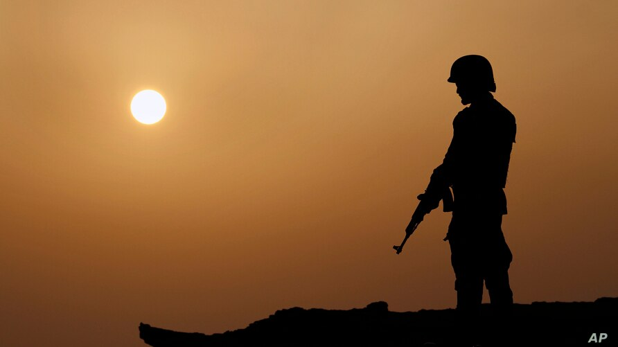 A Pakistan Navy soldier is silhouetted against sunset while stands guard at a hilltop position near Gwadar port, about 700…