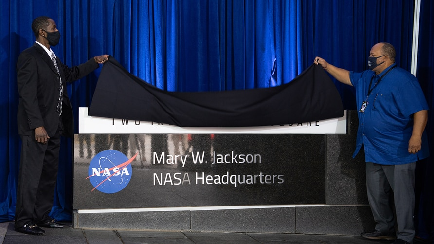 Bryan Jackson, grandson of Mary W. Jackson, left, and Raymond Lewis, son-in-law of Mary W. Jackson, right, unveil the Mary W…