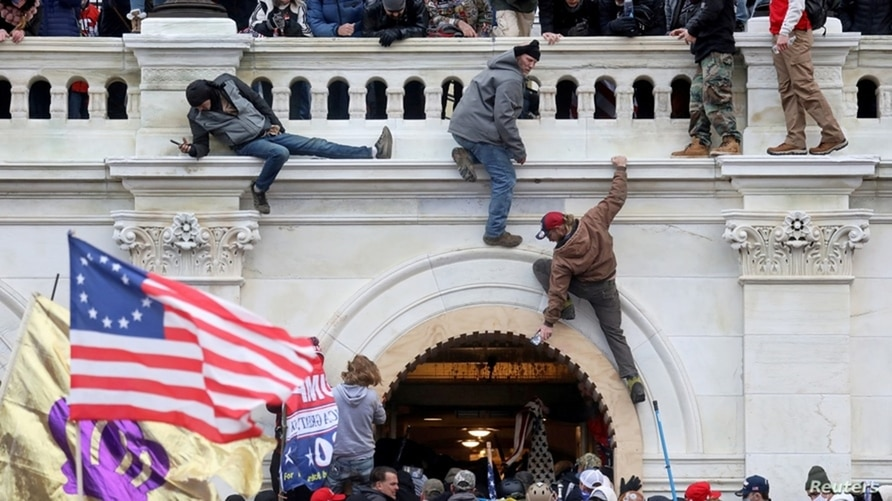 A mob of supporters of U.S. President Donald Trump fight with members of law enforcement at a door they broke open as they storm the U.S. Capitol Building in Washington, Jan. 6, 2021.