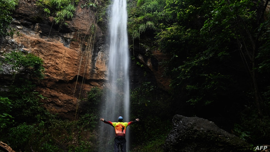 A tourist stands below a waterfall during the gradual reopening of tourism in El Salvador after the mandatory quarantine to…