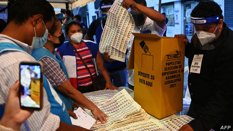 Election officials count ballots after polling stations closed during parliamentary and local elections, in San Salvador, on…