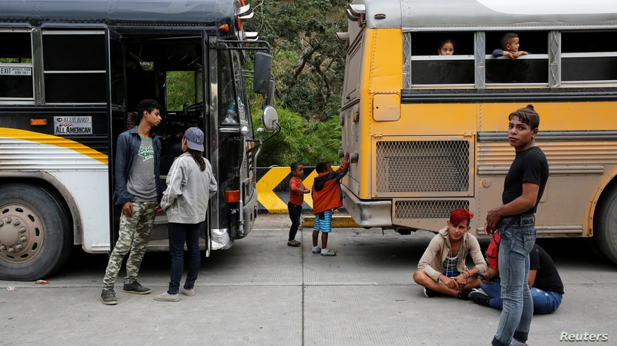 Honduran migrants, who were trying to reach the U.S., wait to get on a bus to return home as children play after being sent…