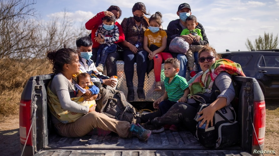 Migrant families and children sit in the back of a police truck for transport after they crossed the Rio Grande River into the…