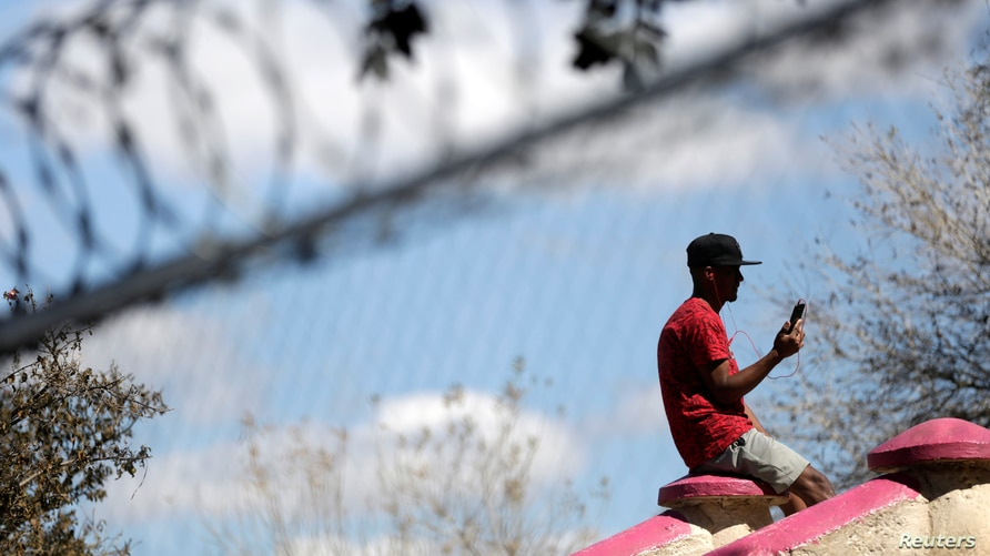 A migrant man who traveled to northern Mexico seeking asylum in the United States, uses his cell phone with headphones at a…