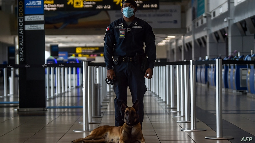 A Panama's Police member controls the check in of a humanitarian flight towards Fort Lauderdale at Tocumen International…