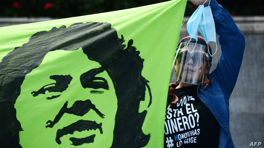 A woman holds a banner depicting Honduran murdered environmentalist Berta Caceres during a protest against the government of…