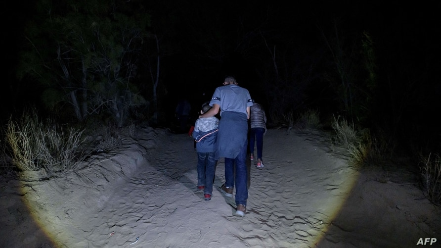 Migrants from Central America, who arrived illegally from Mexico to the US to seek asylum, make their way along a track to turn…