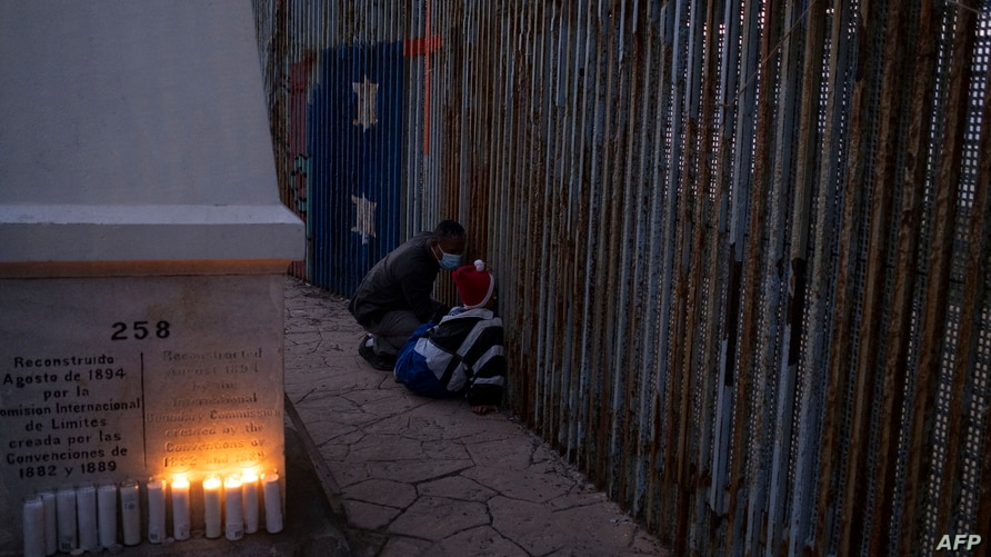 Migrants look through the US/Mexico border fence during a vigil to protest against the death of Salvadoran migrant Victoria…