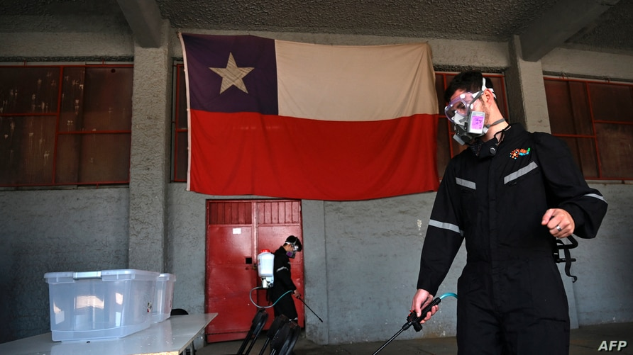 (FILES) In this file photo taken on October 24, 2020 workers disinfect a polling station on the eve of a nationwide…