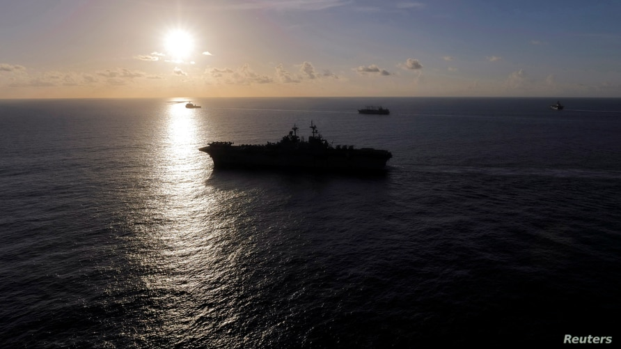 The USS Kearsarge (front) joins other U.S. Navy vessels in maneuvering around Hurricane Maria before eventually returning to…