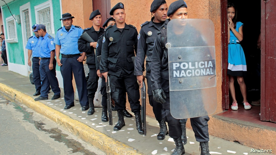 Riot police officers stand near the church where a religious service was carried out for demonstrators who died in a clash…