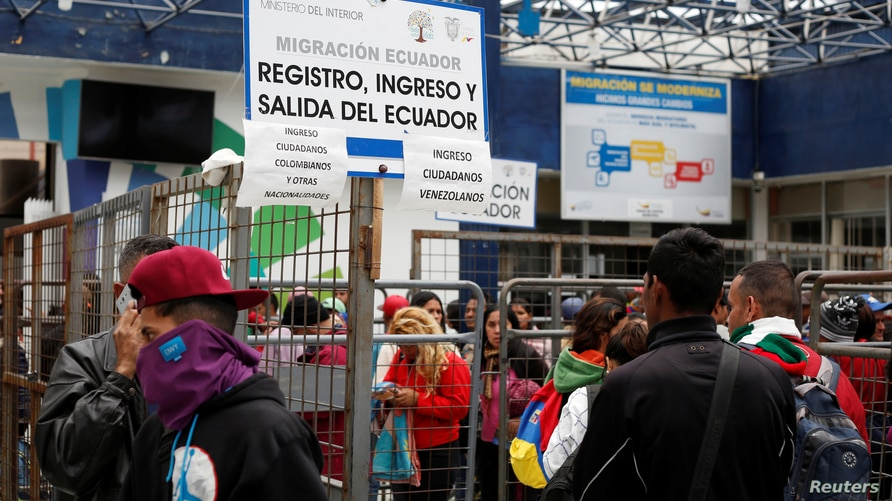 Venezuelan citizens and other migrants wait at the border with Colombia, at the Rumichaca bridge checkpoint, in Ecuador August…