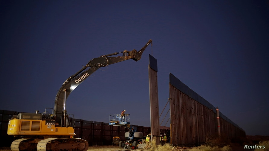 Members of a construction crew using heavy machinery work on a new section of the bollard-type border wall in Sunland Park, New…