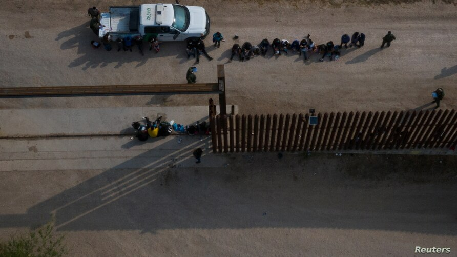 Asylum-seeking unaccompanied minors sit in a line near a U.S. border patrol vehicle after being separated by agents from family…