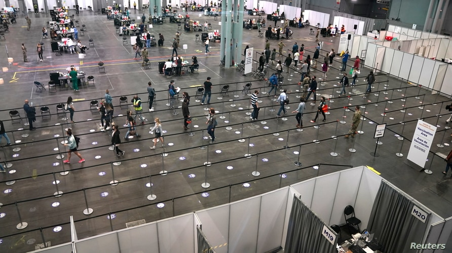 People stand in line at the Jacob K. Javits Convention Center Vaccination Center as Governor Andrew M. Cuomo announces the…