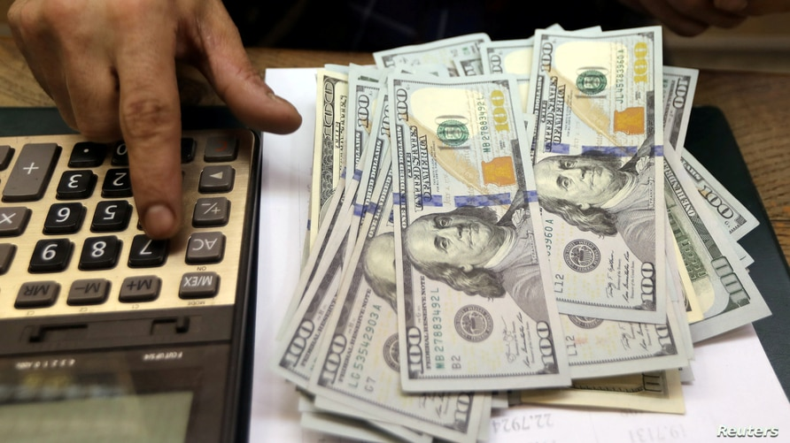 FILE PHOTO: An employee counts U.S. dollar bills at a money exchange in central Cairo, Egypt, March 20, 2019. REUTERS/Mohamed…