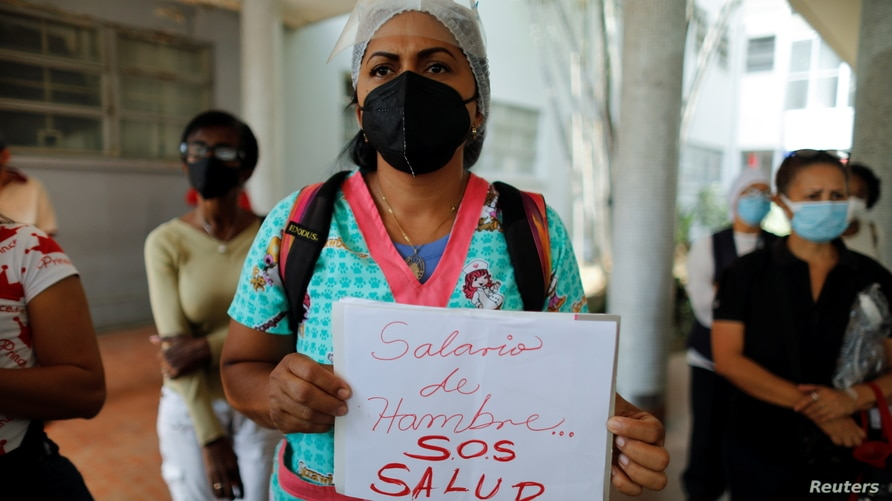 """A health worker holds a sign reading """"Starvation wages, SOS Health"""" during a protest against the lack of vaccines against the…"""