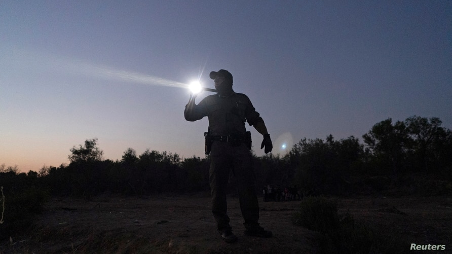 A Texas State Trooper officer looks out, using a flash light, for migrants crossing the Rio Grande in Roma, Texas, U.S. April 8…