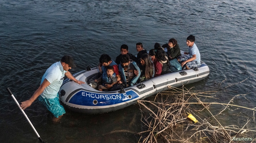Asylum-seeking migrants' families ride on an inflatable raft to cross the Rio Grande river into the United States from Mexico…