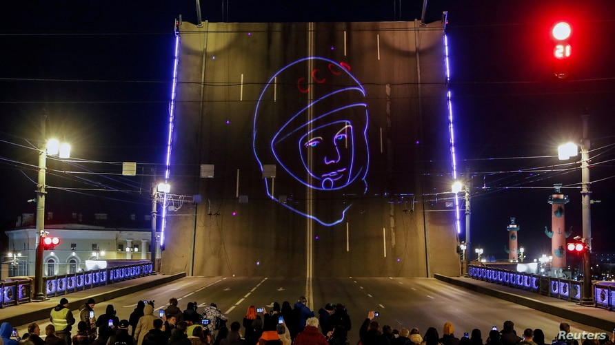Spectators watch a projection of Yuri Gagarin's portrait to mark the 60th anniversary of the first human space flight in Saint…