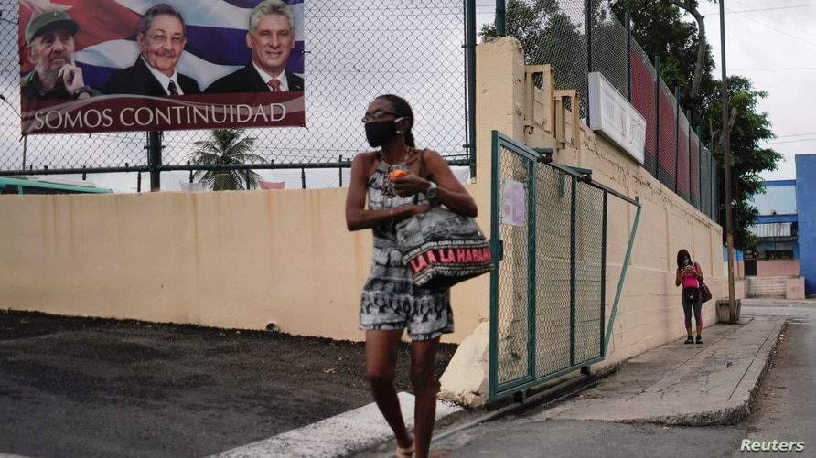 A woman passes by a poster displaying images of late Cuban President Fidel Castro, Cuba's First Secretary of the Communist…