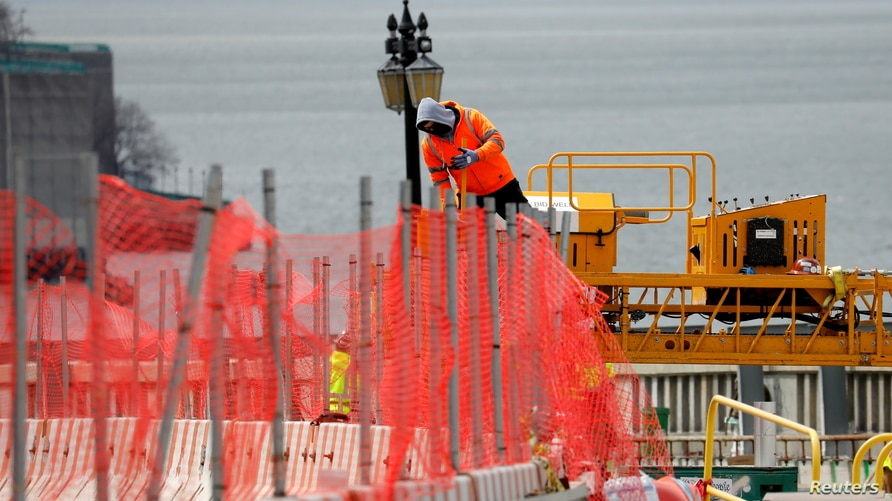 A construction worker climbs above a line of fencing at the site of a large public infrastructure reconstruction project of an…