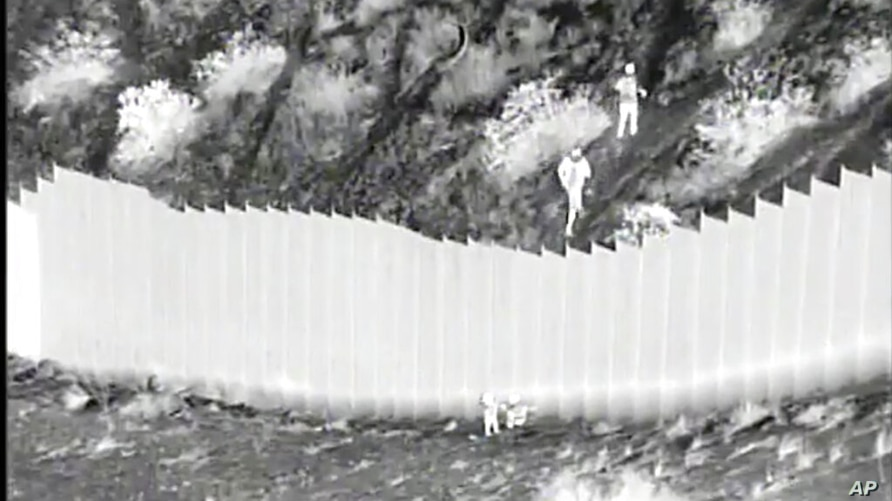 This Tuesday, March 30, 2021, photo taken from night video provided by the U.S. Customs and Border Protection shows smugglers,…