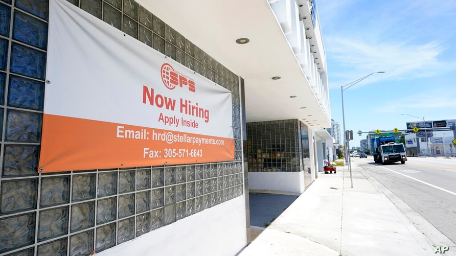 "A ""Now Hiring"" sign is shown outside a business, Wednesday, April 7, 2021, in Miami.  The number of Americans applying for…"