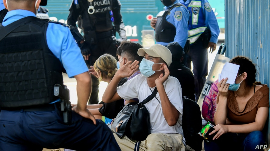 Migrants heading for the US are questioned by police in Corinto, Honduras, on March 30, 2021 before trying to cross the border…